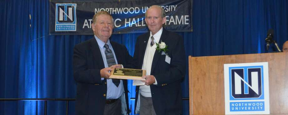 Dick Harmon (right) is presented with his Northwood University Athletic Hall of Fame plaque by former NU football coach Bill Johnston in Oct. 2016. Photo: Timberwolves.gonorthwood.com