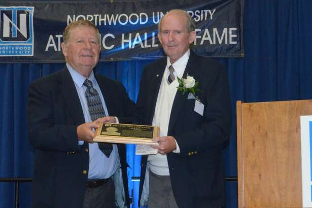 Dick Harmon (right) is presented with his Northwood University Athletic Hall of Fame plaque by former NU football coach Bill Johnston in Oct. 2016.