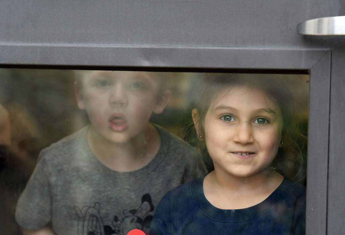 Dereck Slagel, left, and Violet Diggs, right, look out of their daycare window at the YMCA KidzLodge Early Learning Center on Thursday, April 9, 2020, in Clifton Park, N.Y. (Will Waldron/Times Union)