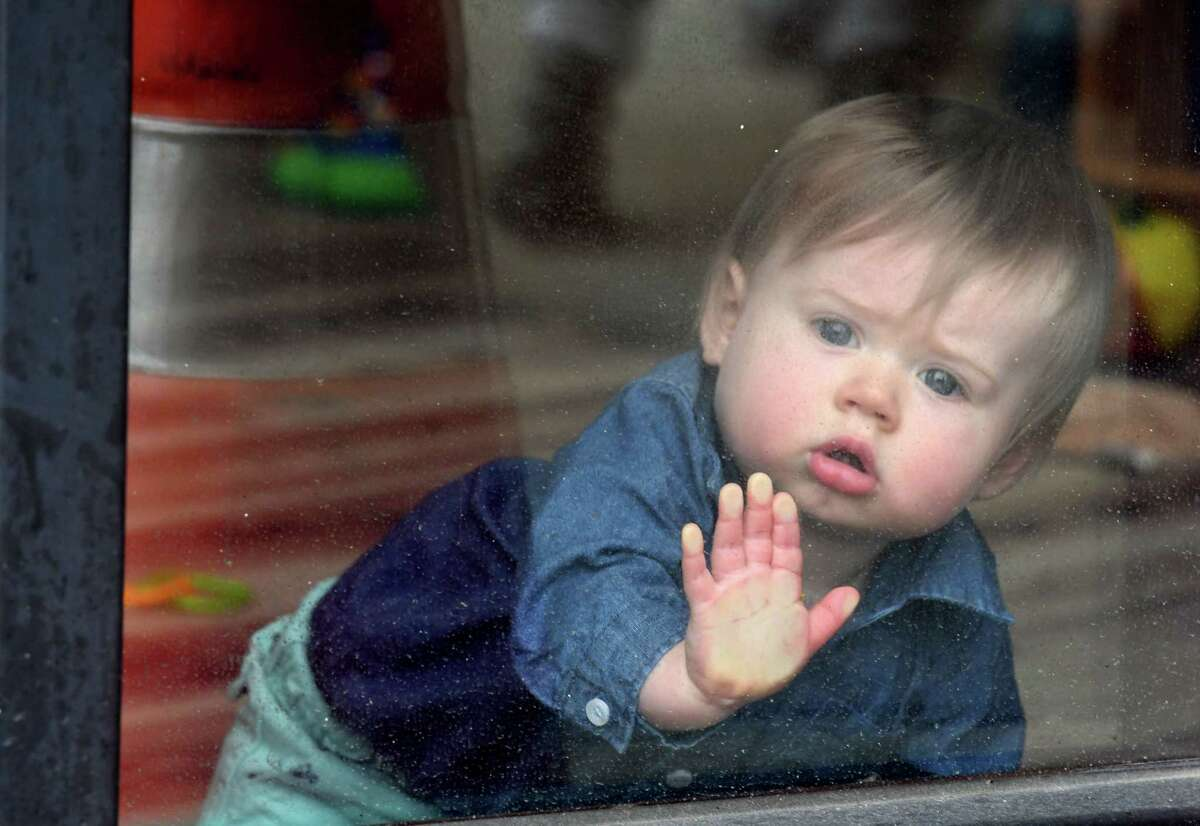 Easton Gillespie, 10 months, peers out of daycare window at the YMCA KidzLodge Early Learning Center on Thursday, April 9, 2020, in Clifton Park, N.Y. (Will Waldron/Times Union)