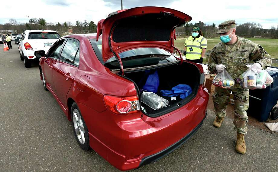 Sgt. First Class Felix Guiffra of the Connecticut Army National Guard puts food into the trunk of a car as  families wait in their cars at Hamden Middle School April 8  to get  food donations from the Christ For Bread of Life parish Catholic church in Hamden and the Connecticut Food Bank. More than 350 families received the groceries. Photo: Peter Hvizdak / Hearst Connecticut Media / New Haven Register