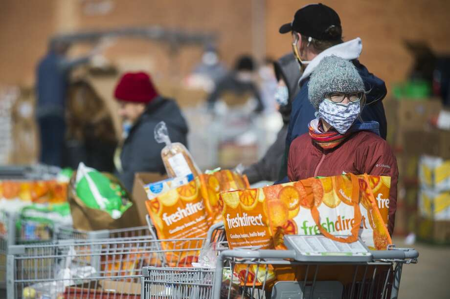 Volunteers load food items into vehicles during a mobile food pantry hosted by the Midland County Emergency Food Pantry Network Thursday, April 9, 2020 at Midland High School. (Katy Kildee/kkildee@mdn.net) Photo: (Katy Kildee/kkildee@mdn.net)