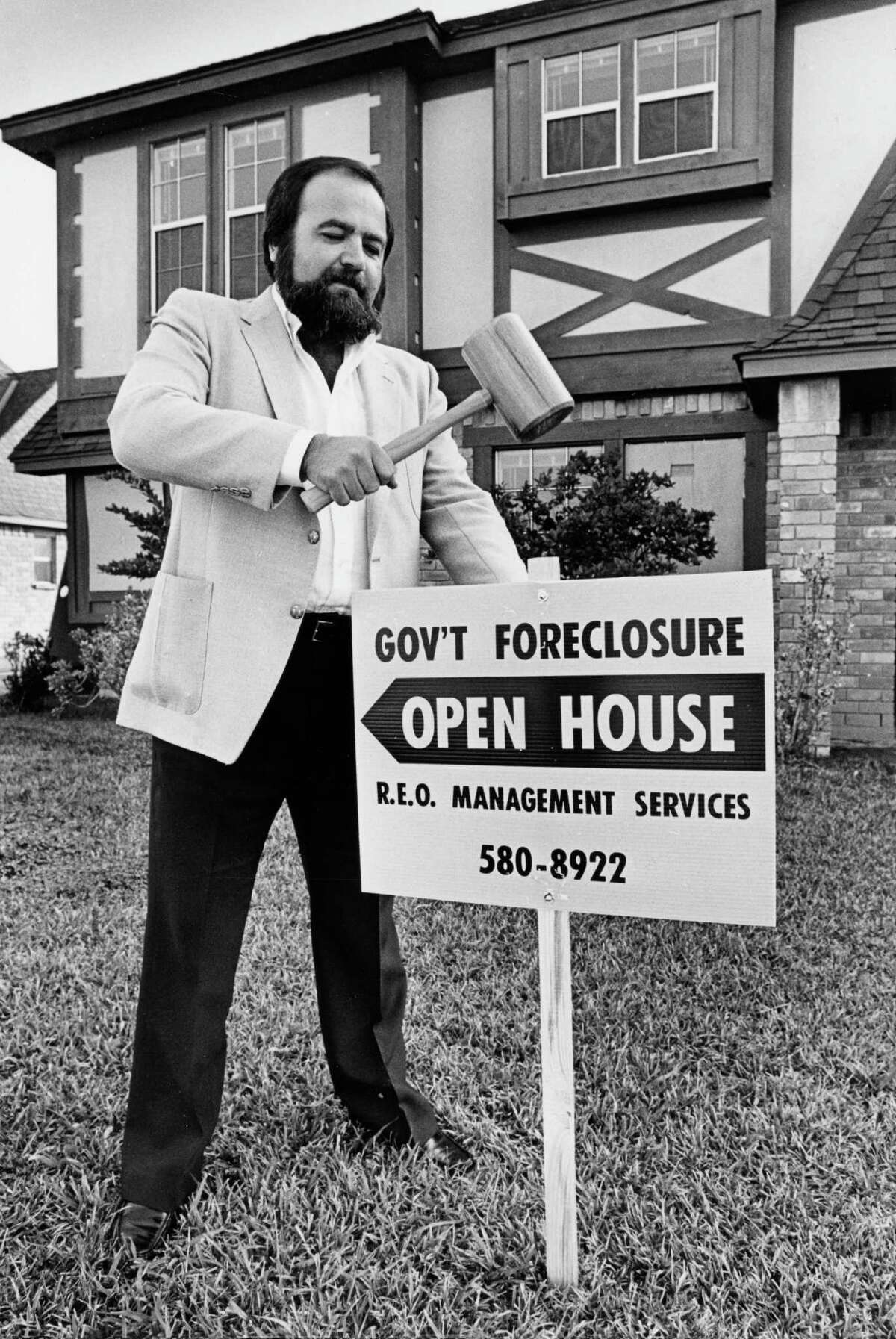 February 7, 1986: Harry Bradley of R.E.Q. Management Services installs a foreclosure sign on a residential property in preparation for a VA foreclosure auction taking place Feb. 8, 1986 in Houston.
