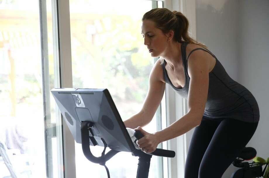Jen Van Santvoord rides her Peloton exercise bike at her home on April 07, 2020 in San Anselmo, California. More people are turning to Peloton due shelter-in-place orders because of the coronavirus (COVID-19). The Peloton stock has continued to rise over recent weeks even as most of the stock market has plummeted. Photo: Ezra Shaw/Getty Images / 2020 Getty Images