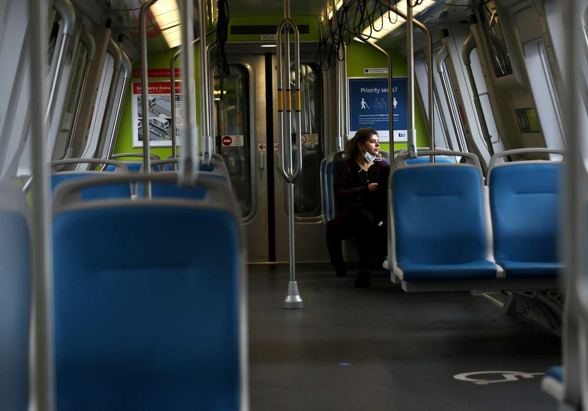 A Bay Area Rapid Transit (BART) passenger rides in an empty train car on April 08, 2020, in San Francisco, Calif.