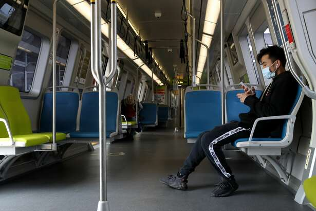 A Bay Area Rapid Transit (BART) passenger wears a protective mask while riding on a train on April 08, 2020 in San Francisco, California. BART announced that it is slashing daily service as ridership falls dramatically due to the coronavirus shelter in place order. Starting Wednesday, regular Monday through Friday service will be reduced to running trains every half hour between 5 am and 9 pm.