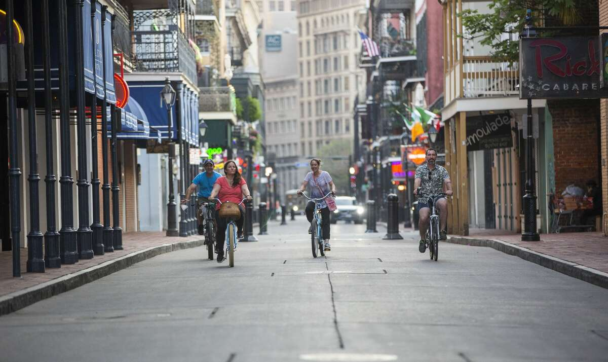 People ride bicycles along a nearly empty Bourbon Street in New Orleans, Louisiana, U.S., on Wednesday, April 8, 2020.