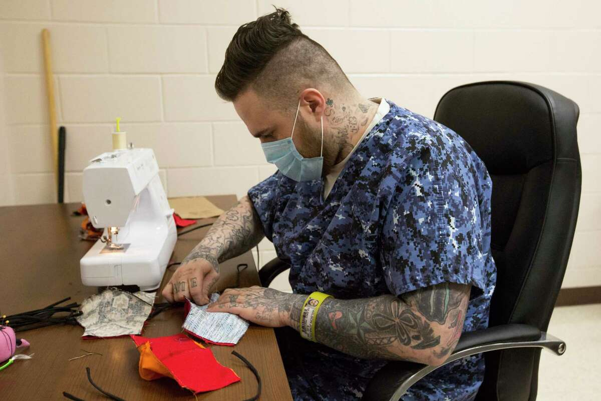 Fort Bend County Jail veteran inmate Jonathon Wilson (CQ) sews a cloth mask in the workroom Thursday, April 9, 2020, in Richmond. The Fort Bend County Detention's sewing program started making face masks that will be distributed to all inmates and jail employees on April 6.