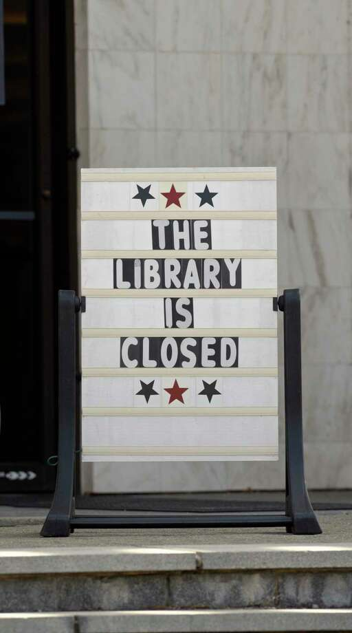 A sign at the entrance to the Danbury Public Library announces that it is closed. Wednesday afternoon, March 18, 2020, in Danbury, Conn. Photo: H John Voorhees III / Hearst Connecticut Media / The News-Times