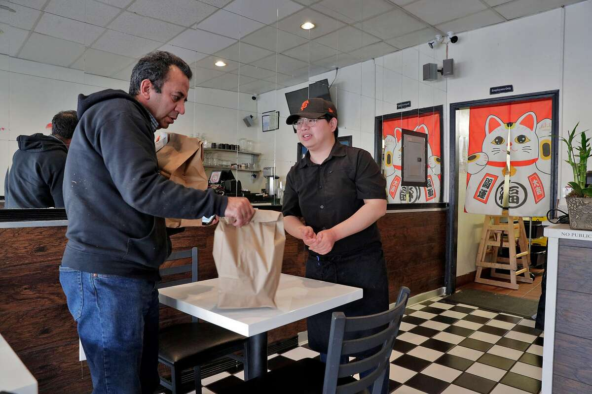 Wathanyu Sae-Kang give a delivery order to driver Fawzi Hameedat, left, at Dozo Ramen restaurant in Oakland, Calif., on Tuesday, March 17, 2020 as residents take advantage of open restaurants for take-out and delivery orders after being told to shelter in place to curtail the spread of the Covid-19 virus in the 6 Bay Area counties.