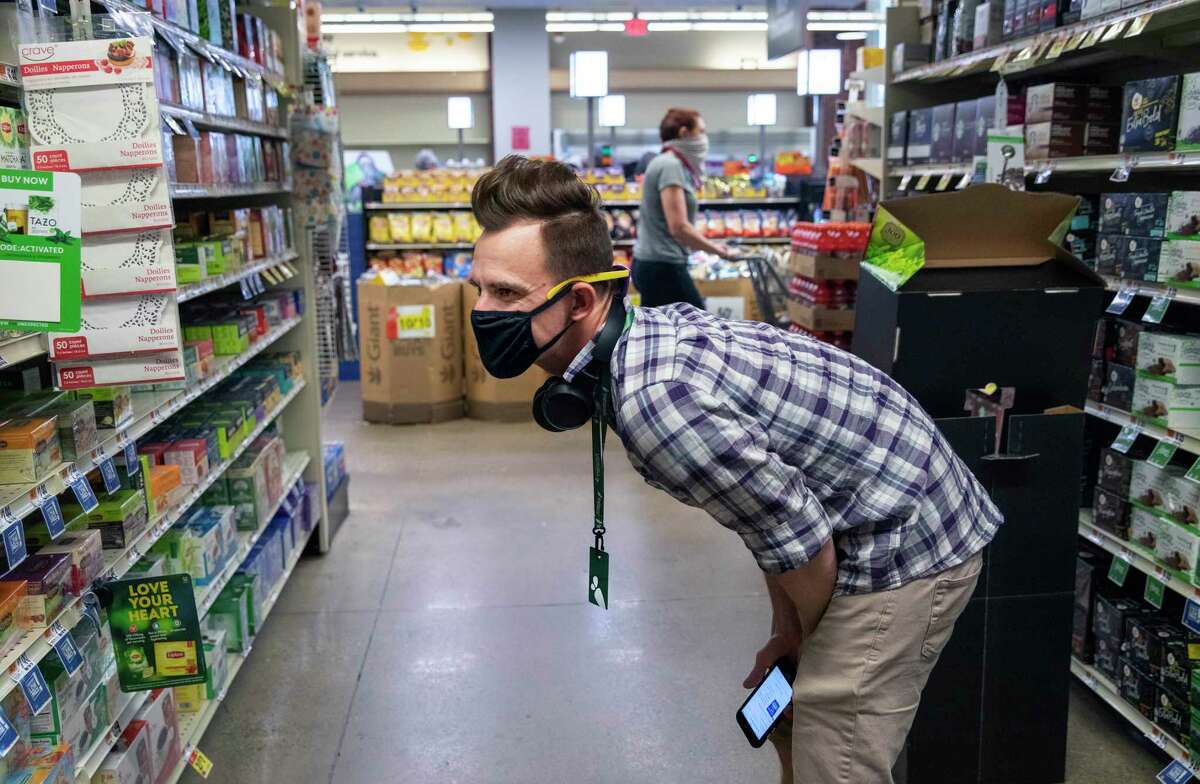 Matt Gillette, a 36 year-old Instacart shopper, fulfills an order at a Washington supermarket in Washington on Monday, April 6, 2020.