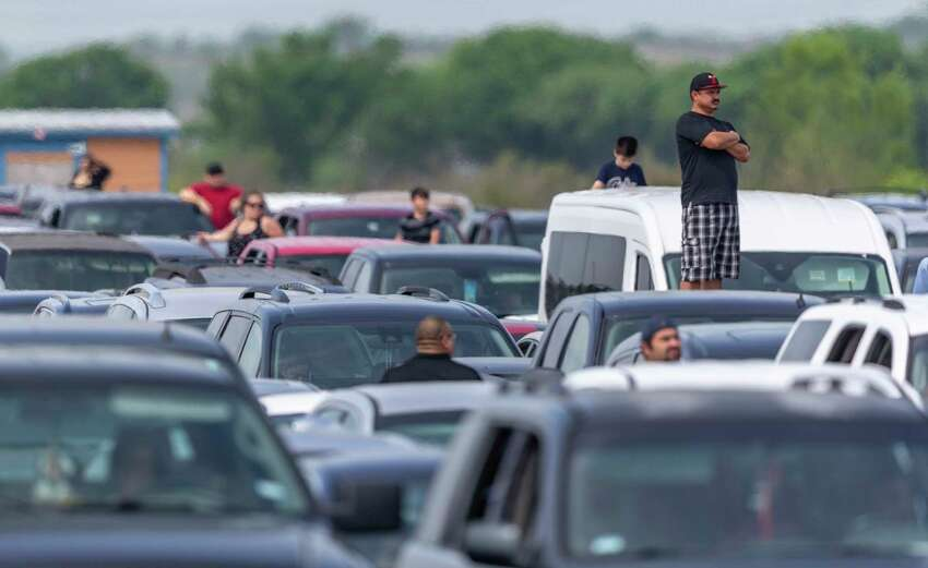 People wait Thursday at Traders Village for the San Antonio Food Bank to begin food distribution.