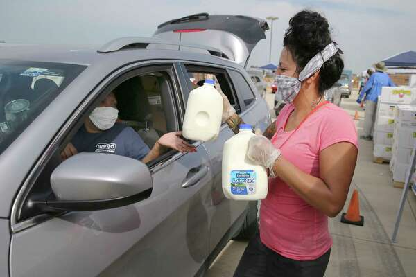 Heather Martinez greets and hands over two gallons of milk as thousands of people in cars - some waiting since late yesterday afternoon - gather at Traders Village to get food from the San Antonio Food Bank on Thursday, Apr. 9, 2020.