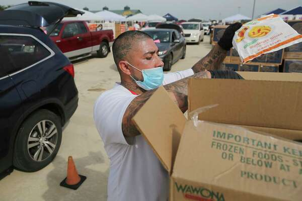 Anthony Gaitan picks up bags of peaches to load into a vehicle.