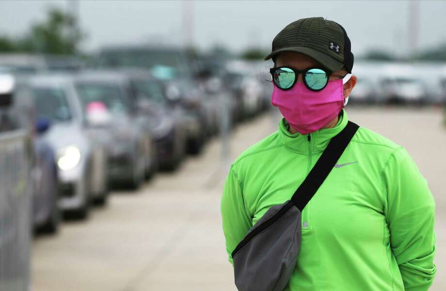 Veronica Hernandez with the San Antonio Food Bank wears a mask and sunglasses as thousands of people in cars gather at Traders Village. Lines of cars extended for miles as 400 volunteers got ready to distributed items such as milk, bread, vegetables and even Easter candy. Photo: Kin Man Hui, Staff Photographer / **MANDATORY CREDIT FOR PHOTOGRAPHER AND SAN ANTONIO EXPRESS-NEWS/NO SALES/MAGS OUT/ TV OUT