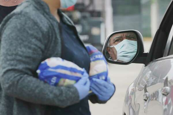 Helpers place food in the back of a car of a man seen wearing a mask in his mirror.