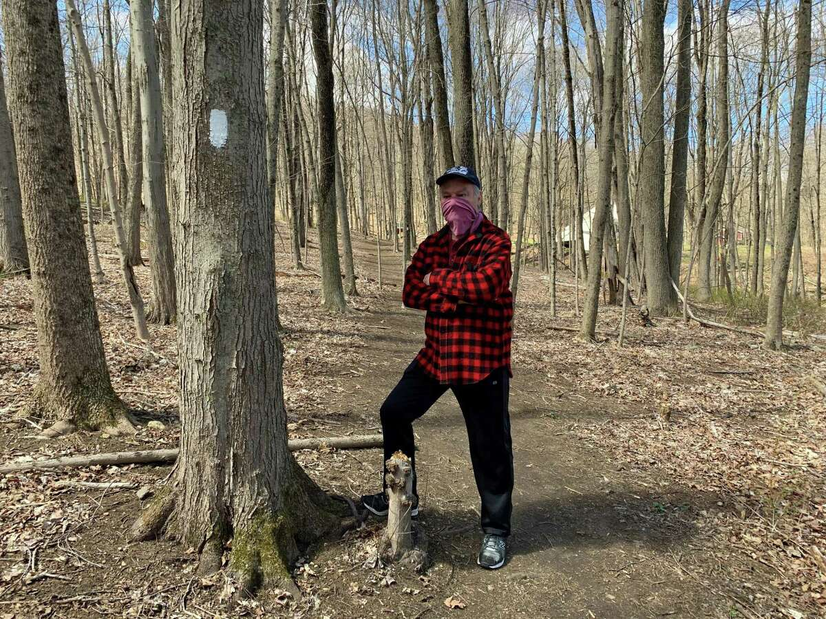 Hiking along the white trail at the Stephenson Nature Preserve in Bethel Saturday, Jim Smith wears a homemade mask.