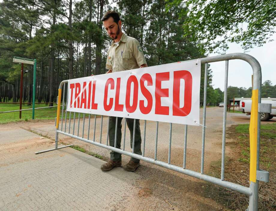 Forester Connor Murnane places a barricade at a trailhead at William Goodrich Jones State Forest after Gov. Greg Abbott announced the state's parks and historic sites will temporarily close at 5 p.m., Tuesday, April 7, 2020, in Conroe. Montgomery County saw another big jump in the number of COVID-19 cases Thursday bringing the county's total to 231. Photo: Jason Fochtman