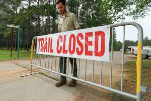 Forester Connor Murnane places a barricade at a trailhead at William Goodrich Jones State Forest after Gov. Greg Abbott announced the state's parks and historic sites will temporarily close at 5 p.m., Tuesday, April 7, 2020, in Conroe. Montgomery County saw another big jump in the number of COVID-19 cases Thursday bringing the county's total to 231.