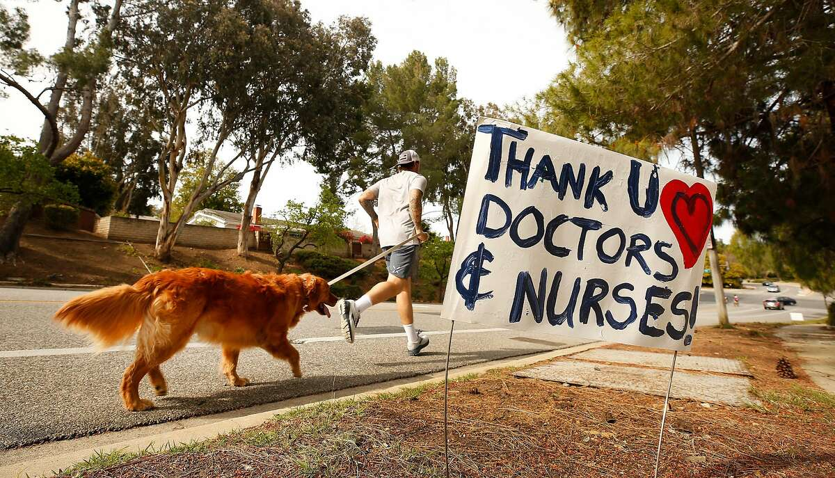 LOS ANGELES, CA - MARCH 31, 2020 A jogger with his dog runs past Los Robles Hospital & Medical Center in Thousand Oaks Tuesday March 31, 2020 where signs of encouragement and praise for healthcare workers battling the coronavirus Covid19 pandemic have been placed along Lynn Road and Janss Road en route to Los Robles Hospital & Medical Center. The signs were created by Trevor Quirk, a Ventura attorney who ran for office, using leftover campaign signs w the