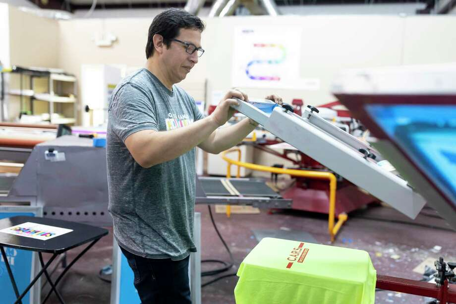 Rocky Castillo, owner of Green Mango Graphics in Conroe, demonstrates the screen printing process, Thursday, April 9, 2020.Proceeds from their initiative to assist local businesses will be evenly disbursed between the local business and Green Mango Graphics. Photo: Gustavo Huerta, Houston Chronicle / Staff Photographer / Houston Chronicle © 2020