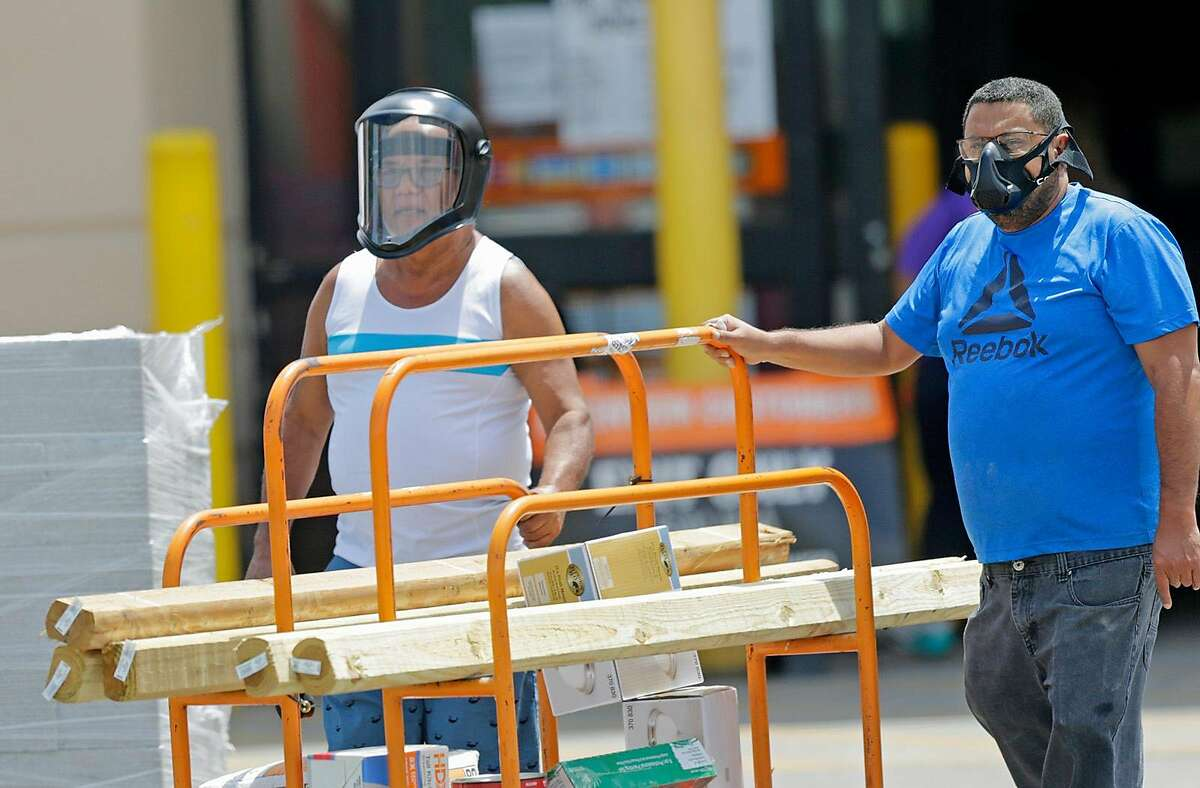From left to right, Jose Ramon Mejias and his relative Edwin Cruz pushing a cart with purchases as they wearing a protective mask at the Home Depot located at 3030 SW 8th St, in Miami, Florida as the coronavirus pandemic continues on Monday, April 6, 2020. (DAVID SANTIAGO/Miami Herald/TNS)