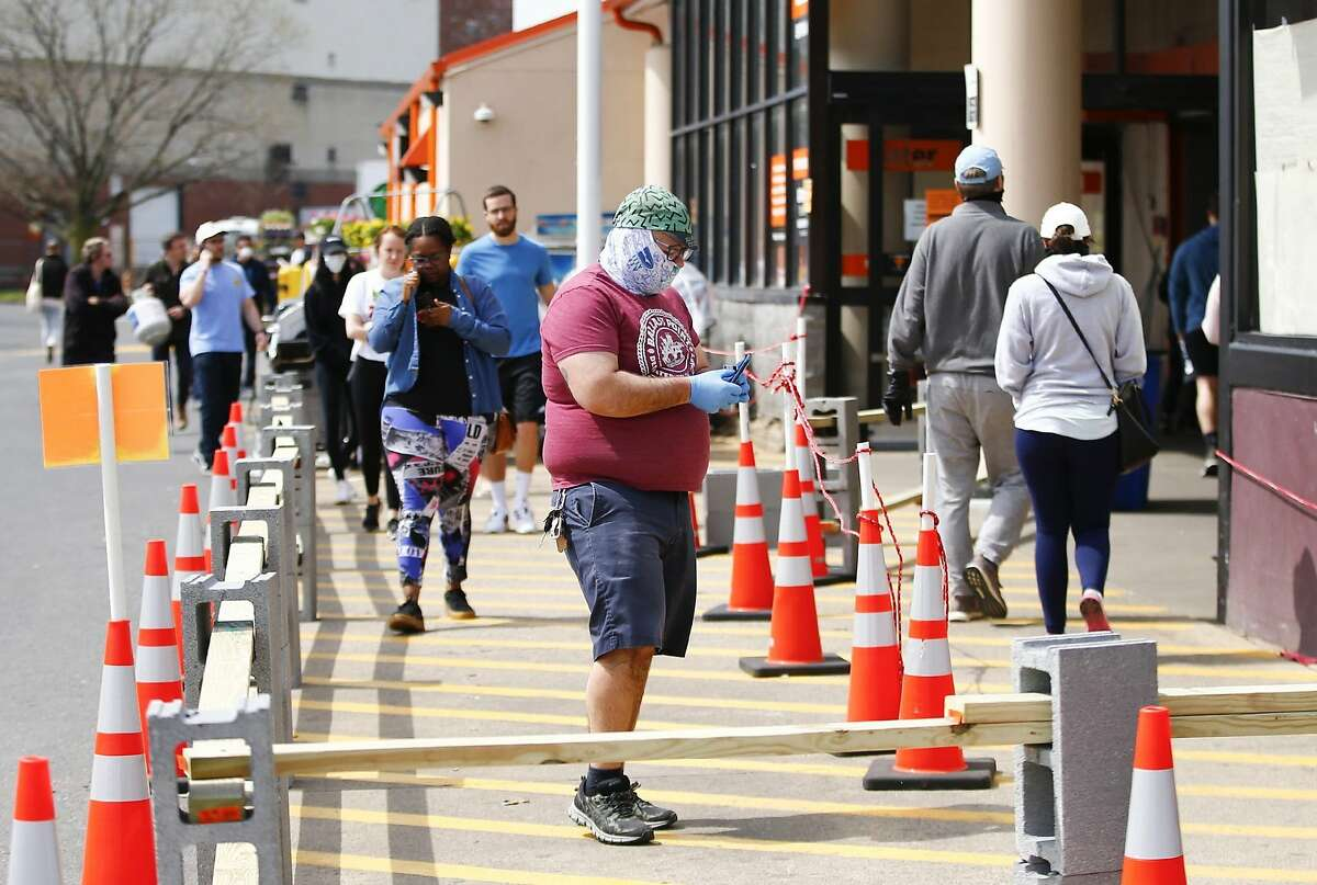 Shoppers at The Home Depot, on Christopher Columbus Boulevard in South Philadelphia, wait in line before entering, Sunday, April 5, 2020. The store is only allowing a limited number of customers inside at a time during business hours to help facilitate social distancing due to the new coronavirus. (Yong Kim/The Philadelphia Inquirer via AP)