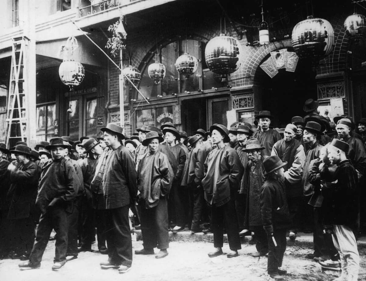 A group of men stand in the street below paper lanterns outside the Yuen Fat & Co. premises in Chinatown, San Francisco in 1901.