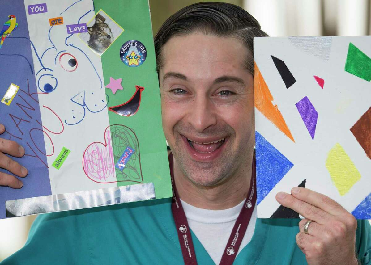 Shriners Hospitals for Children in Houston Child Life Assistant Chris Sallans, who prefers to be called Mr. Chris, poses for a portrait with arts and crafts he created in YouTube videos for patients to watch at home.