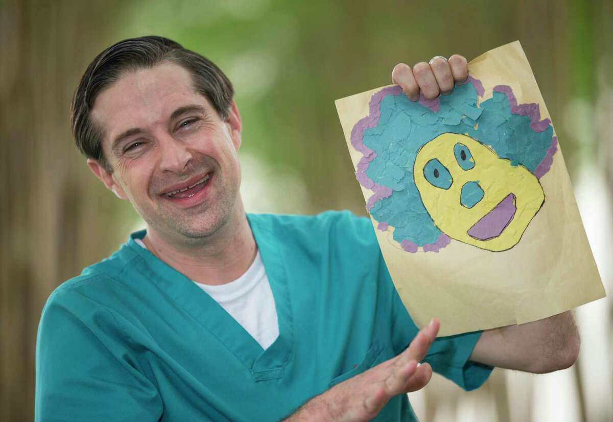 Shriners Hospitals for Children in Houston Child Life Assistant Chris Sallans poses for a portrait with arts and crafts he created in YouTube videos for patients to watch at home Wednesday, April 8, 2020, in Houston.