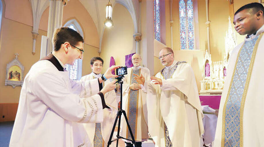 Brother Leland Thorpe, left, sets up a camera in a test run for Sunday's live streaming of Easter Mass, as he jokes with the priests of St. Mary's Catholic Church in Alton Thursday. From left are Frs. Pauls Nguyen, David Beauregard, Jeremy Paulin and Ben Unachukwu.