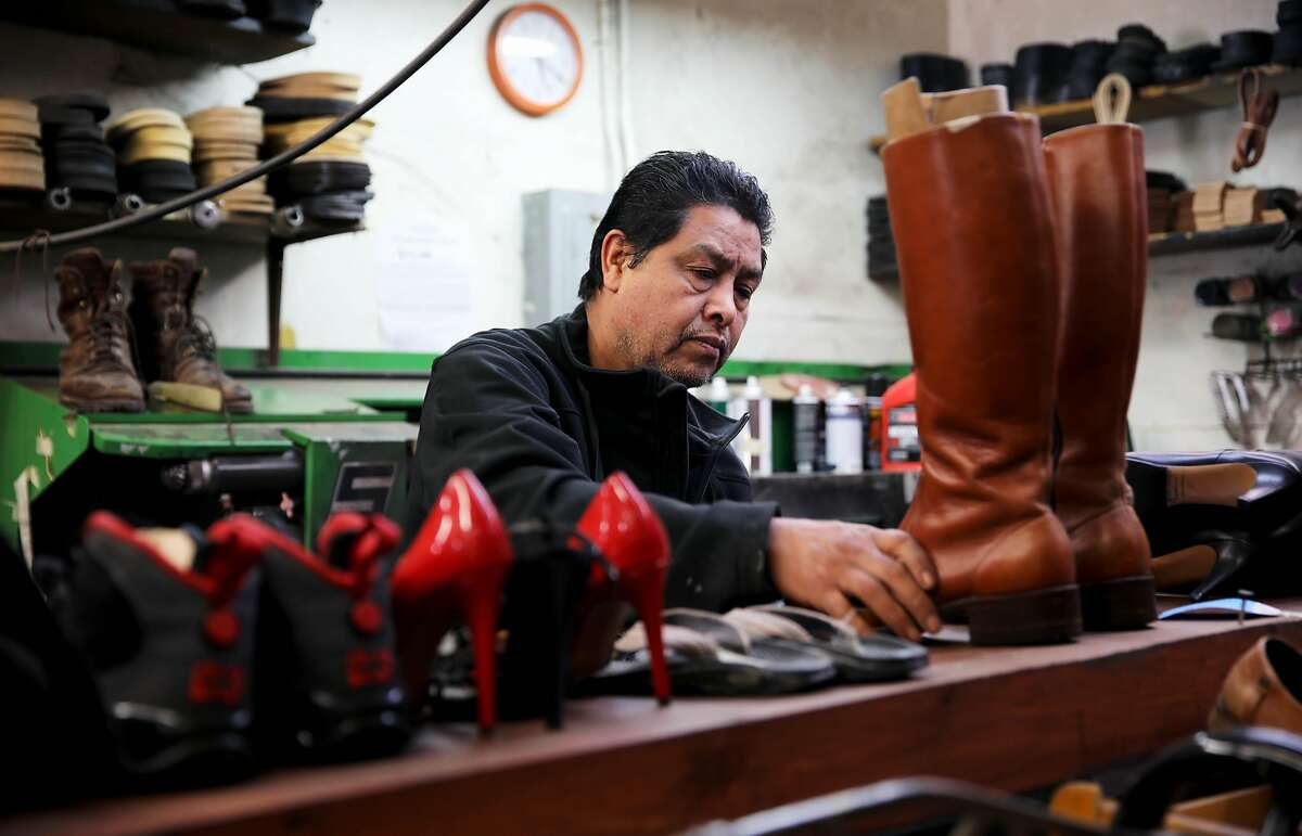 Gerardo Pena, the owner of Right Way Shoe Repair, located at 5479 College Ave., works inside the shop on Tuesday, April 7, 2020, in Oakland, Calif. Pena can't pay this month's $2,700 in rent for the College Avenue location, a shop he's owned for 16 years. Same with the $2,300 he owes for Shoe Clinic on Piedmont Avenue. But this isn't about a business struggling to survive. This is about generations of families, particularly low-income and immigrant families, being impacted by the coronavirus. Pena has $500 in his bank. That's for food, his daughter, Leslie Pena, said.