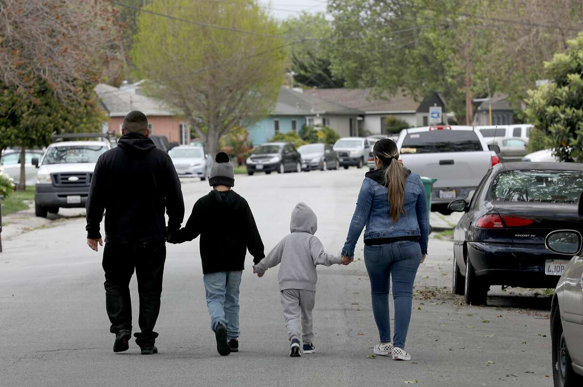 Christian (left) and his wife Monze (right) were laid off from restaurant jobs in mid-March and not qualified to receive unemployment because they are undocumented immigrants as they walk with their 9 and 4 year old sons on Thursday, April 9, 2020, in San Lorenzo, Calif.