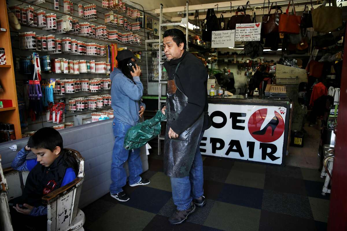 Sammy Pena, Jr., 8, left, watches a show on a phone as his aunt, Leslie Pena, and grandfather, Gerardo Pena, work inside Right Way Shoe Repair, located at 5479 College Ave., on Tuesday, April 7, 2020, in Oakland, Calif. The shop's owner, Gerardo Pena, can't pay this month's $2,700 in rent for the College Avenue location, a shop he's owned for 16 years. Same with the $2,300 he owes for Shoe Clinic on Piedmont Avenue. But this isn't about a business struggling to survive. This is about generations of families, particularly low-income and immigrant families, being impacted by the coronavirus. Pena has $500 in his bank. That's for food, his daughter, Leslie Pena, said.