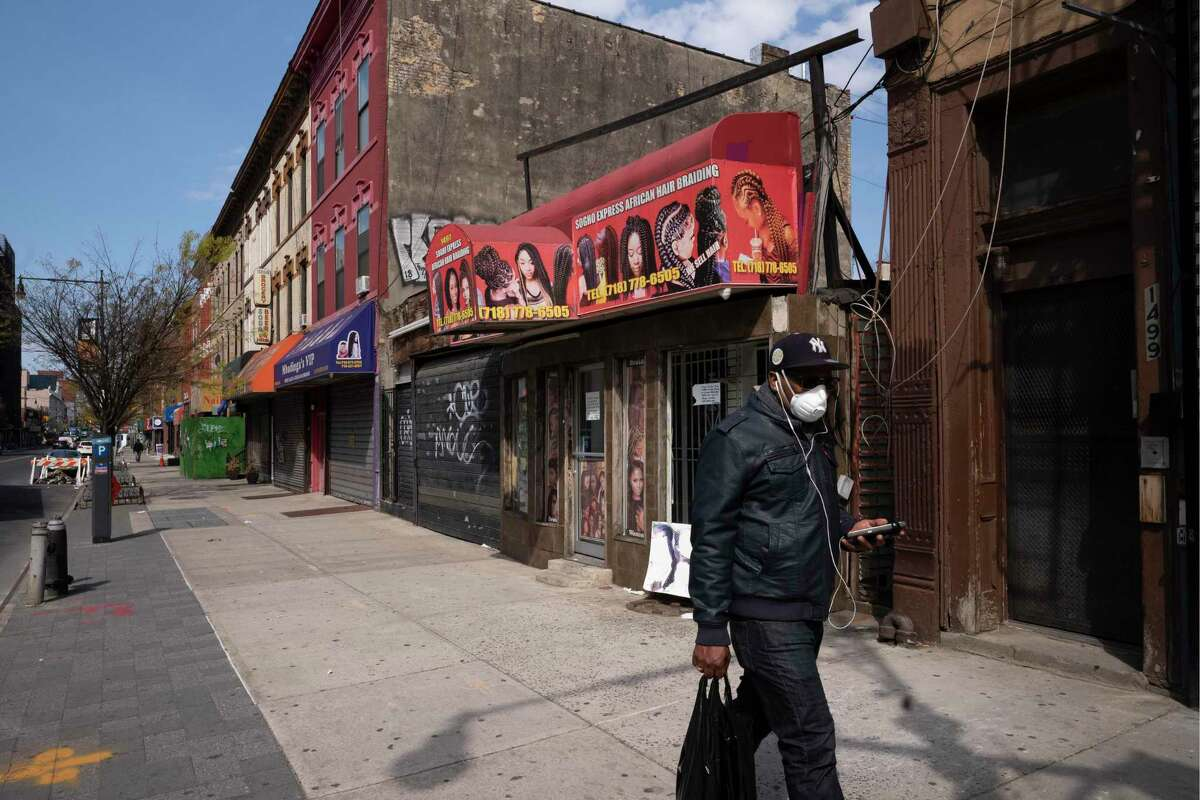 A man wearing a mask walks past Sogho Express African Hair Braiding salon, which is closed due to the coronavirus pandemic, Tuesday, April 7, 2020 in the Bedford Stuyvesant neighborhood of New York. (AP Photo/Mark Lennihan)