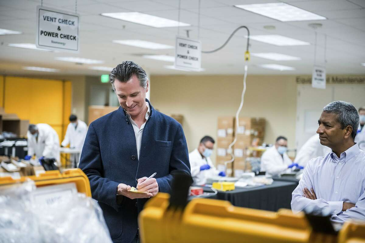 FILE - In this March 28, 2020, file photo, Bloom Energy CEO KR Sridhar, right, watches as California Gov. Gavin Newsom writes down a note during a tour with Sridhar of the Bloom Energy Sunnyvale, Calif., campus. Bloom Energy is a fuel cell generator company that has switched over to refurbishing ventilators as an increasing number of patients experience respiratory issues as a result of COVID-19. Gove. Newsom announced Monday, April 6, 2020, the state would loan 500 ventilators to the national stockpile for use by New York and other states experiencing a crush of coronavirus-related hospitalizations. (Beth LaBerge/Pool Photo via AP, File)