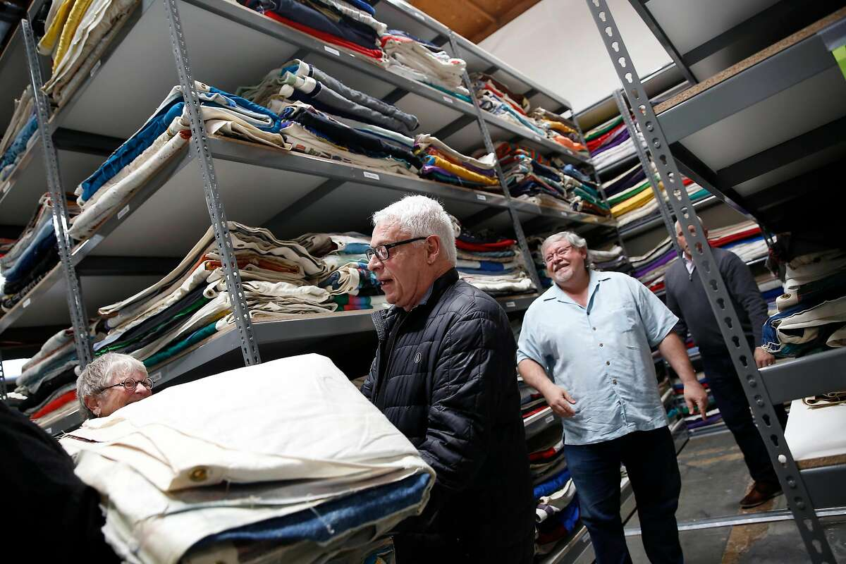 Cleve Jones (center), one of the original founders of the AIDS Memorial Quilt, carries a quilt recently arrived from Atlanta at a National AIDS Memorial Grove warehouse on Tuesday, February 18, 2020 in San Leandro, Calif.