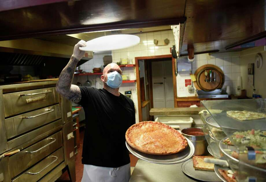 Co-owner Frankie Ferraro makes a pizza while wearing a mask and gloves at Glenville Pizza in the Glenville section of Greenwich, Conn. Thursday, April 9, 2020. As an extra measure to prevent the spread of coronavirus, Greenwich is mandating food service workers to wear a protective mask and gloves at work. Photo: Tyler Sizemore / Hearst Connecticut Media / Greenwich Time