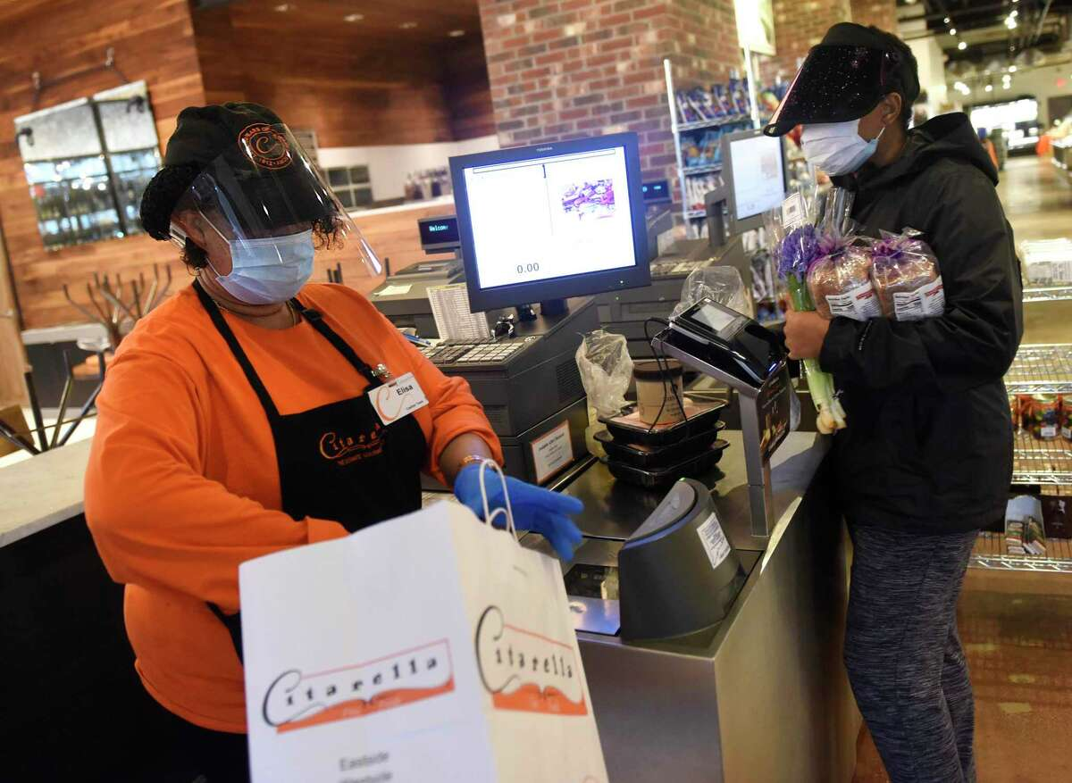 Citarella cashier Elisa Oliphant wears a mask and gloves with assiting customer Michelle Parris, of Greenwich, at Citarella Gourmet Market in Greenwich, Conn. Thursday, April 9, 2020.