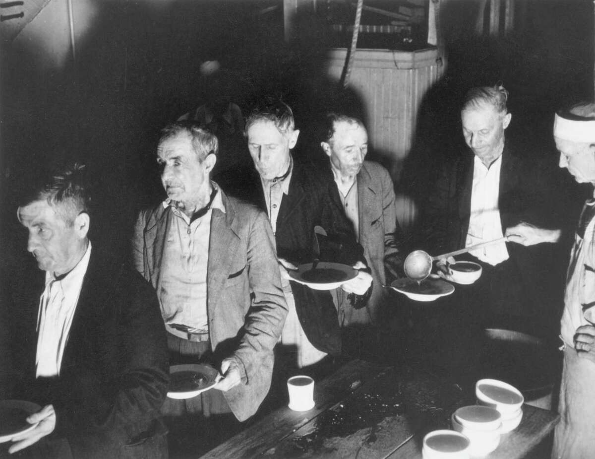 Impoverished men waiting on a soup line for a meal during the Depression.