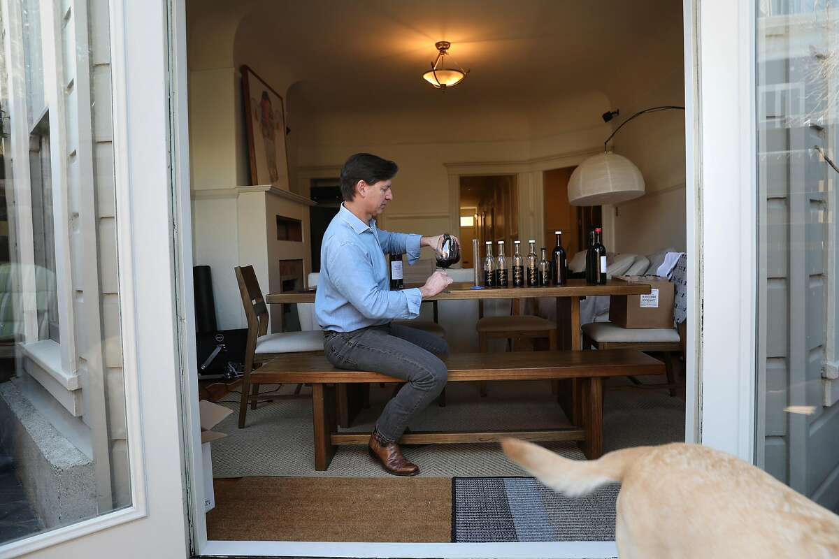 Wine entrepreneur Cameron Hughes pours one of his wine bottles received in bulk at his dining room table at home on Wednesday, March 11, 2020, in San Francisco, Calif. PHOTOS EMBARGOED UNTIL FURTHER NOTICE