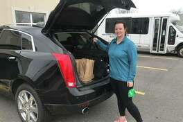 Beth Schumacher from the Edwardsville Junior Service Club helps deliver meals to Main Street Community Center clients on Tuesday. With the center closed due to the COVID-19 pandemic, the center has expanded its food delivery program.