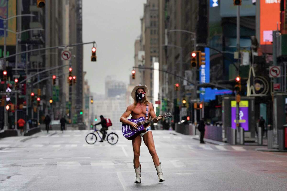 """Street performer Robert John Burck, known as The Naked Cowboy, poses for photos in New York's Times Square, Thursday, April 9, 2020, during the coronavirus epidemic. He is wearing a mask and his guitar is adorned with stickers that read, """"Trump Keep America Great."""" (AP Photo/Mark Lennihan)"""