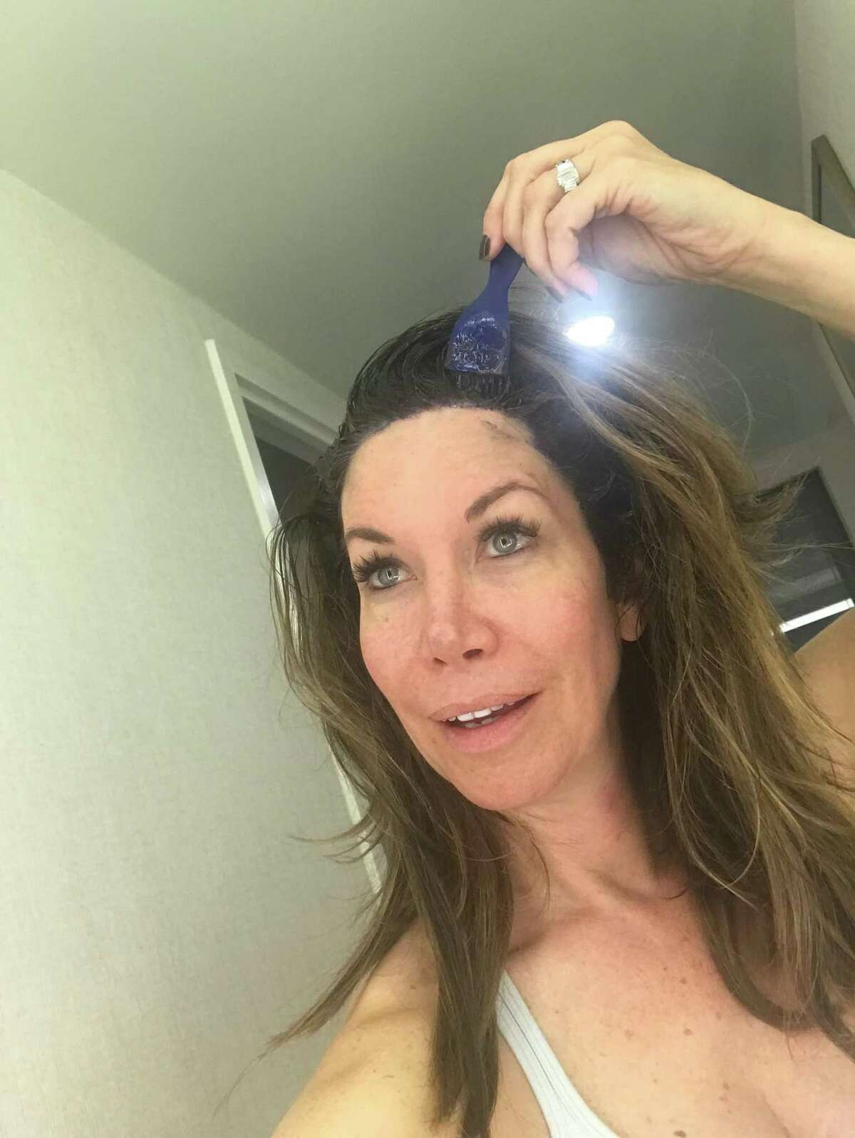 BEFORE: Roseann Rogers, sales manager for Stewart Title and former TV personality, shows how she dyed her roots at at home.