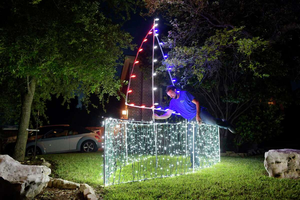 Hunter Hinson-Heart adjusts a sailboat made from PVC pipe, commercial-grade LED lights and Christmas lights on Wednesday, April 8, 2020. Hinson-Heart and his wife, Heather, are creating free stick figure lighting scenarios in the front yards of some homes on their street.