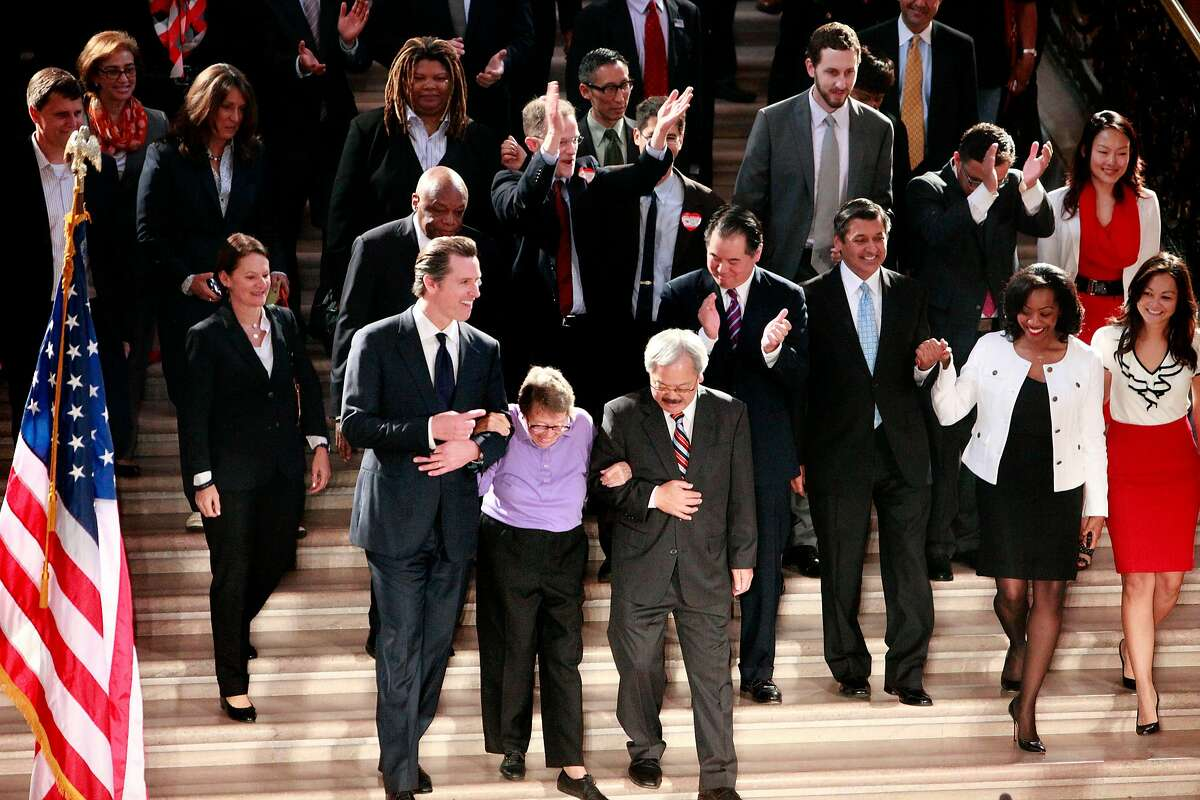 Lieutenant Governor Gavin Newsom (front left) and Mayor Ed Lee (front right) escort Phyllis Lyon (front center) as they walk down the steps in the rotunda at City Hall for a press conference after the Supreme Court handed down their decisions on Wednesday, June 26, 2013 in San Francisco, Calif. The Supreme Court handed down their decisions dismissing California's Proposition 8 and striking down the Defense of Marriage Act.