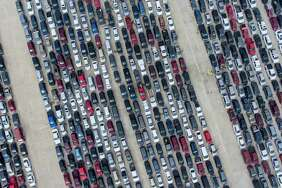 People wait in their cars, April 9, at Traders Village for the San Antonio Food Bank to begin food distribution.