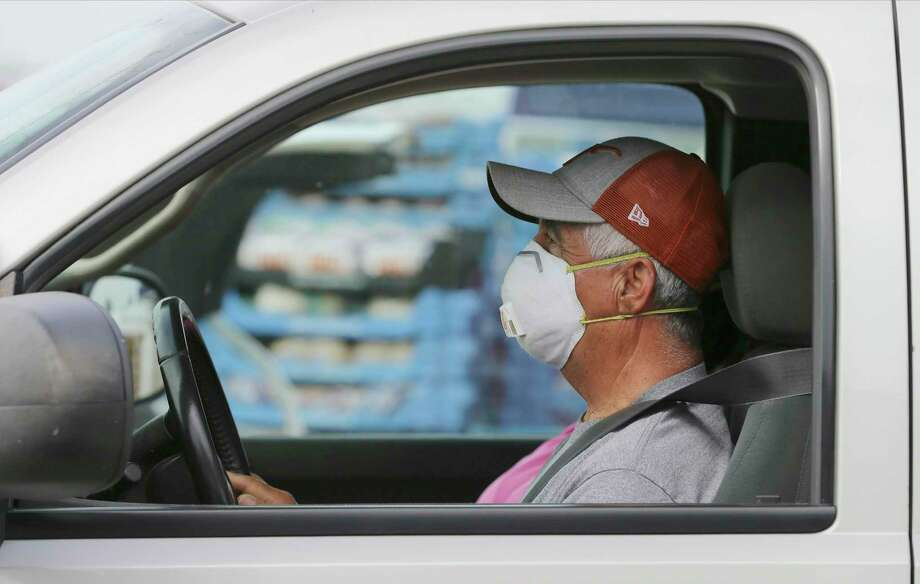 A man wears a mask while waiting to get food at Traders Village from the San Antonio Food Bank on Thursday, Apr. 9, 2020. Photo: Kin Man Hui, San Antonio Express-News / Staff Photographer / **MANDATORY CREDIT FOR PHOTOGRAPHER AND SAN ANTONIO EXPRESS-NEWS/NO SALES/MAGS OUT/ TV OUT