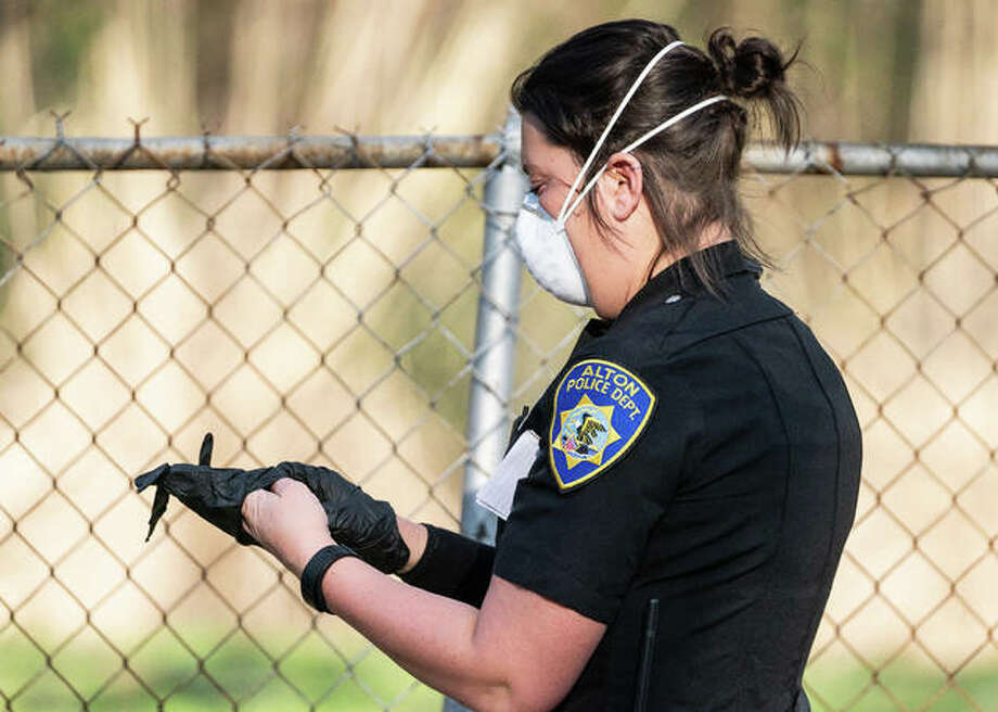"""Wearing a protective mask, Alton police officer Ashley Roever puts on latex gloves as she approaches the scene of a single-vehicle crash Tuesday. While officers do what they can to protect themselves and others from coronavirus spread, Alton Police Chief Jason """"Jake"""" Simmons. Photo: Nathan Woodside 