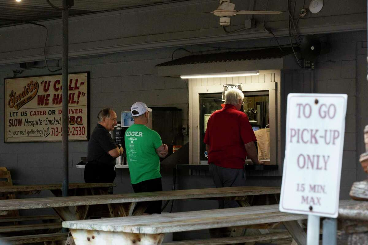 Goode Co. guests pick up orders from the restaurant's window on Monday, March 16, 2020, in Houston.